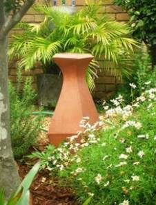 A few easy-care plants, hard surfaces such as gravel instead of lawn, and an eye-catching no-maintenance ornament come together to create a garden that requires very little work to keep looking good.
